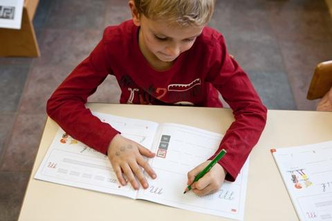 Linkshandige kinderen zien steeds een voorbeeld bij het schrijven van een letter.